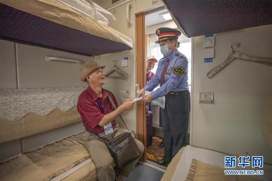 9月8日,在重庆北站,列车工作人员为搭乘跨省旅游专列的旅客发放口罩。