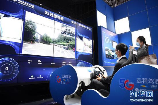 """工作人员在2020线上智博会上演示""""5G远程驾驶技术""""。新华社记者 唐奕 摄"""