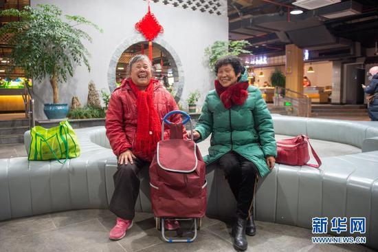 1月5日,在改造完毕的嘉兴市南湖区杨柳湾幸福里菜市场,两名老人在休息区休息。新华社发(江汉 摄)