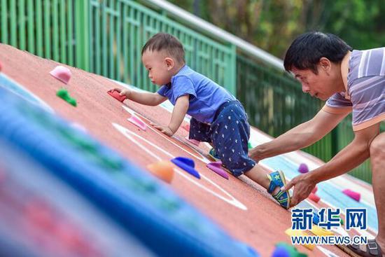 图为市民带着小孩在江北区赵家山体育文化公园玩耍。新华网 发(重庆市规划和自然资源局供图)