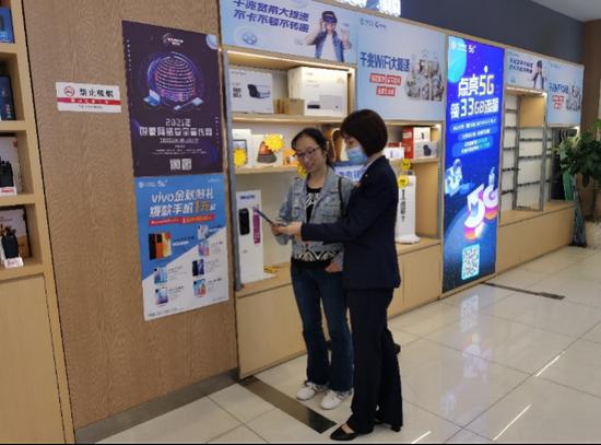 (在重庆移动营业厅,工作人员向市民开展信息安全保护宣传)