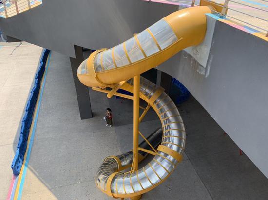 魔幻!重庆一轻轨站外设旋转滑梯 滑着下轻轨站(图)