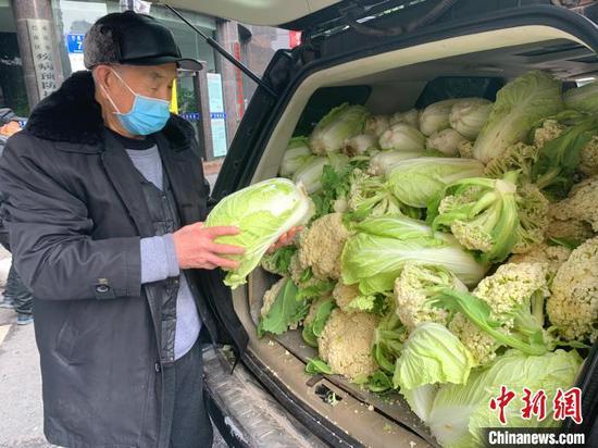 图为徐先恒老人送蔬菜。 钟欣 摄