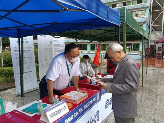 (重庆移动工作人员向市民推广国家反诈中心APP)