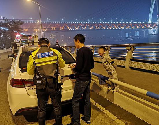 孙某6岁的儿子(右)在一旁教育父亲。 渝中警方 供图