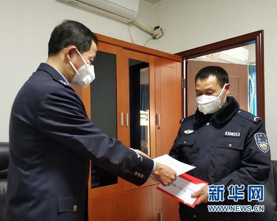 渝北交巡警支队龙溪大队教导员王世平(左)给段辉富发放强制陪护通知书和捐款。新华网 陈雨 摄