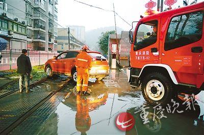 消防车将越野车从铁轨上拖离