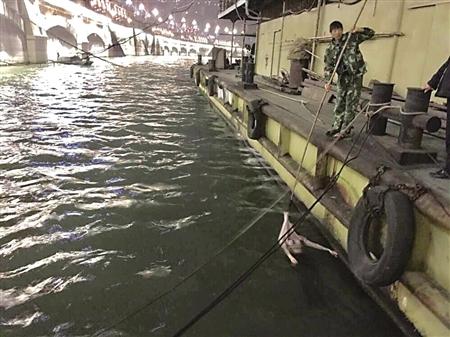 渔民用竹竿钩住女子身上的毛衣,让其头部浮在水面上,并慢慢将其拉向趸船船舷。