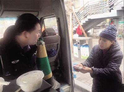 """汪阿姨请民警张伟将300元转交给""""老尹""""。 本报记者 胡杰 摄"""