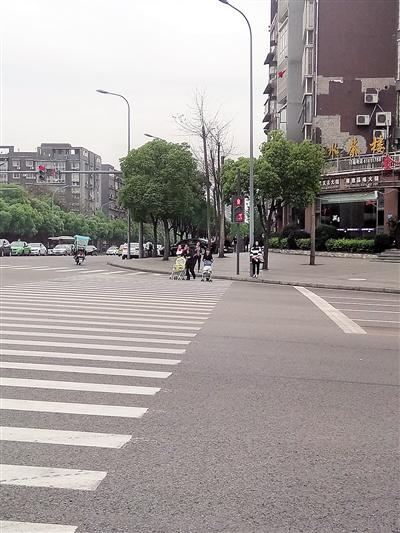 两位推着婴儿车的家长在红灯还有五秒左右时开始穿行。