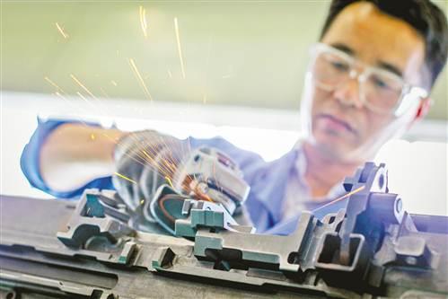 4月18日,重庆望江工业有限公司某生产车间,梅春正在装配特种产品自动机