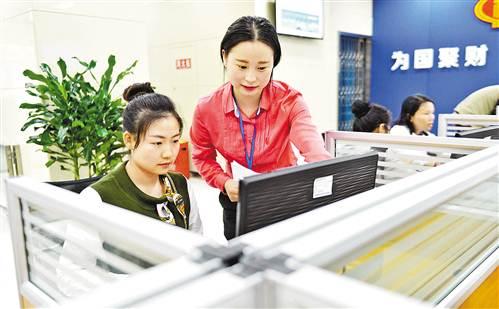 5月10日,九龙坡区行政服务中心,引导员陈菲正在协助市民在网上提交电子材料