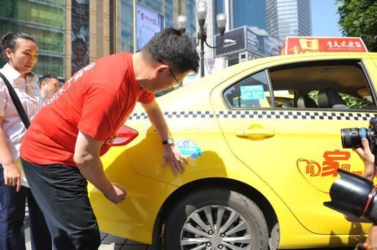 """出租车司机在车上贴上了""""内畅外联·守法有序·文明出行""""拒绝交通陋习的宣传车贴。"""