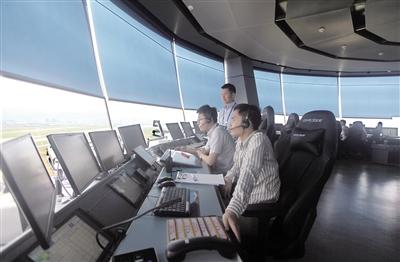 """昨日,江北机场T3塔台投入使用,工作人员在塔台内指挥高空""""交通"""""""