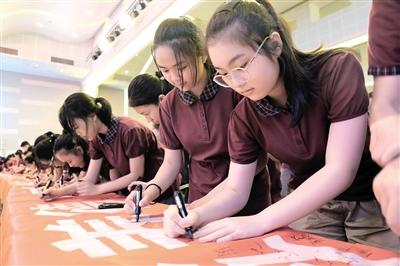 """江北区中学生签字参与""""文明餐桌""""活动。 江北区文明办供图"""