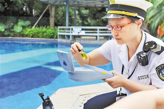 8月10日,在融汇5期游泳池,执法人员正对游泳池水质指标进行现场快检