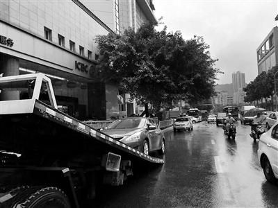 违停的车辆被依法拖移。 本报记者 高科 摄
