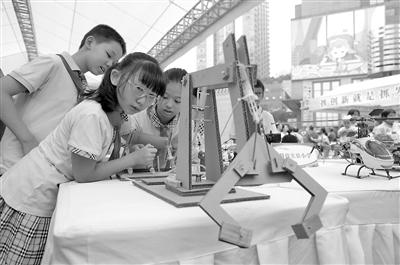 """昨日,江北区""""全国科普日""""主题志愿服务活动现场,秦琬琳制作的液压机械装置科技感实足。本报记者 胡杰 摄"""