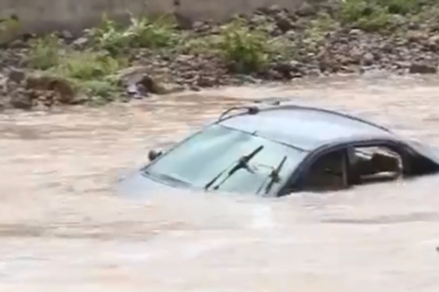 山洪暴发还强行驾车过河 5人被困车顶险被冲走