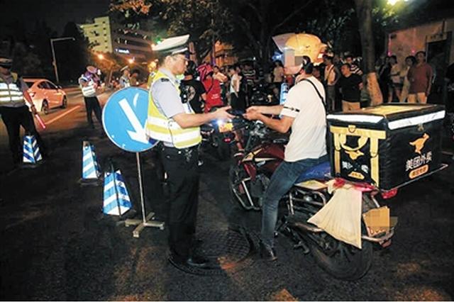 民警在两轮车整治现场进行检查,一外卖小哥被拦下。