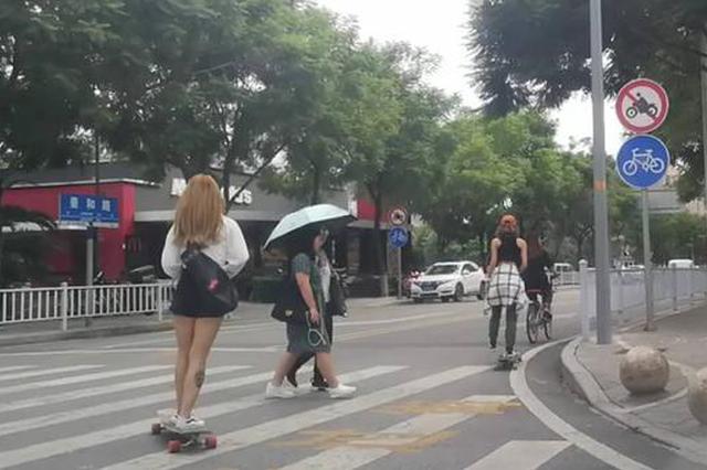 网红美女踩滑板遛马路 边踩边用手机拍视频