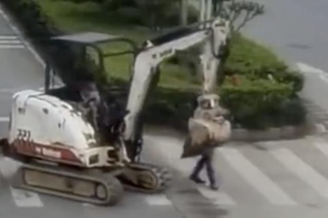 3岁男童开挖掘机上路 亲爹竟还在旁淡定指导