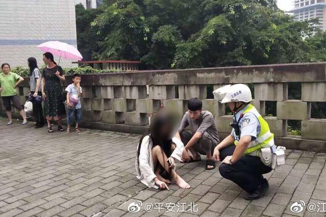 惊险一刻!女子坐护栏想轻生 警民合力救下她(图)