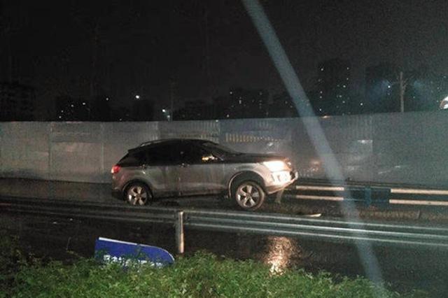 重庆一新手女司机上路开快车 雨天路滑骑上隔离栏