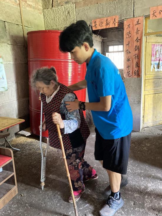 (志愿者搀扶行走困难的老人)