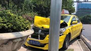 出租车为避撞前车猛撞上路边花坛