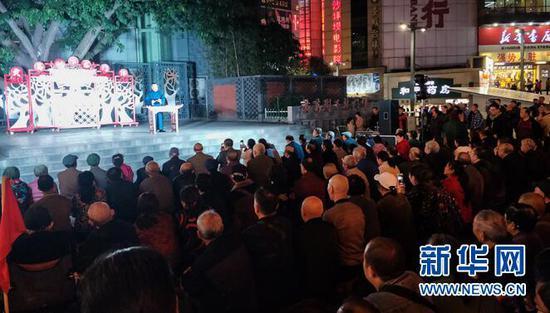 沙坪坝三峡广场黄葛树下聚集大批市民听红色故事会 新华网发(周迎香 摄)