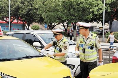 交通执法人员对巡游出租汽车进行检查。