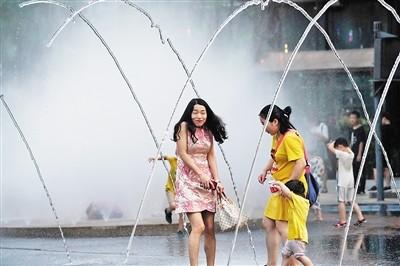 市民兴奋地走在喷泉下。 上游新闻记者 张锦旗 摄