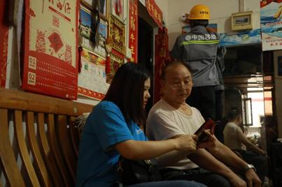 (重庆移动工作人员为老人安装智能烟感设备并指导其使用)