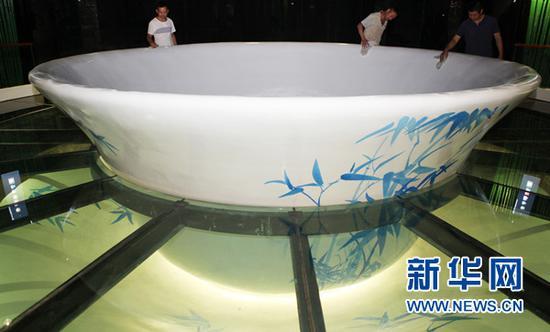永川规划展览馆内,工作人员正在擦拭直径5米的巨型茶碗。新华网发(陈仕川 摄)