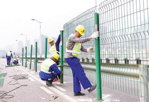 工人正在嘉陵江大桥上安装施工隔离安全网