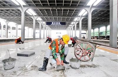 工人们在站台加紧安装地板。