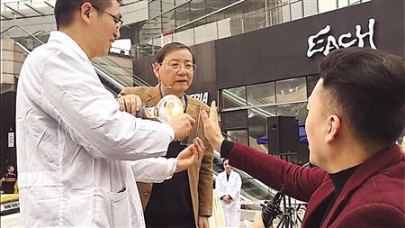 吕长富在教市民辨别产品真假的小妙招 记者 韩政 摄