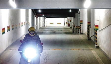 """昨日,渝北区,一辆摩托车通过车库的""""波浪路""""。 首席记者 钟志兵 摄"""