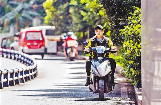 3月8日,外卖女骑手曹珍珍骑着摩托给客户送餐。