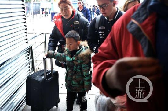 小家伙一脸茫然,不过手里的行李箱还是抓得牢牢的。
