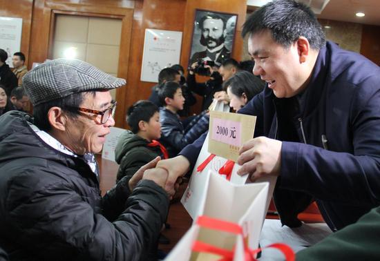 """困难群众代表接受人道救助金和""""博@""""新年福包"""