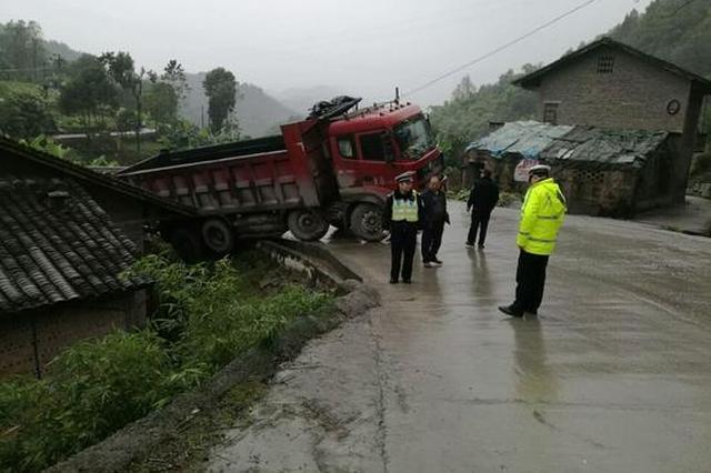 重庆一货车发生侧滑 直接开到路边房顶上