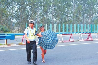 裸奔女在民警守护下离开高速路