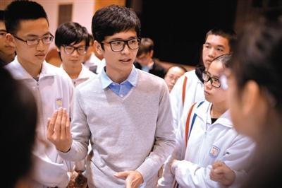 2月7日,王锐旭(左2)在母校的演讲很成功,演讲结束后,王锐旭被学弟学妹围住。 新京报记者 吴江 摄