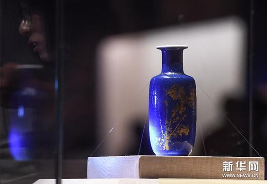 """7月14日,观众在欣赏故宫博物院藏的""""洒蓝釉描金小棒槌瓶""""。"""
