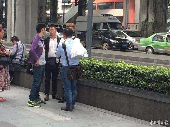 """在店门口,一个小伙儿将刚刚拿到的iPhone""""扛""""在背后,记者询问到,几个袋子中一共有10部新款iPhone!"""
