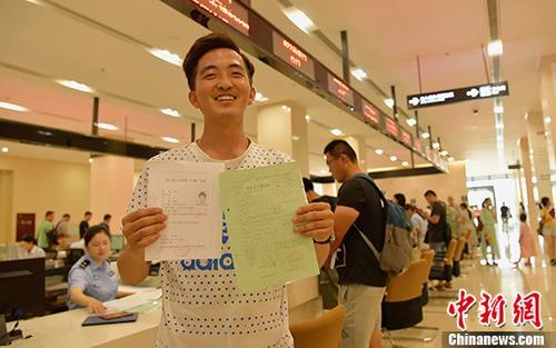 资料图:四川成都,刚毕业的大学生王单办理完手续落户成都。 中新社记者 刘忠俊 摄