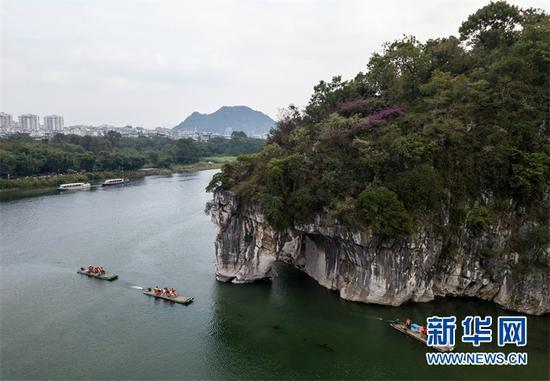 (游人乘船在桂林象鼻山附近游览。 新华社记者李鑫摄)
