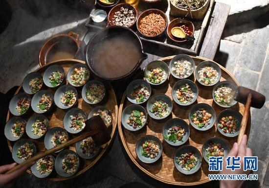 (在广西三江侗族自治县古宜镇,侗族同胞将煮好的油茶打到装好配料的碗里。新华社记者陆波岸摄)